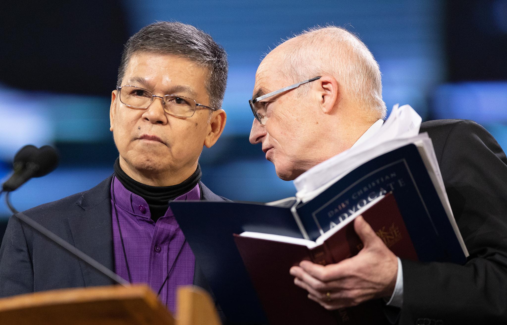 Os Bispos Ciriaco Q. Francisco (à esquerda) e Patrick Streiff conferenciam-se no pódio durante a Conferência Geral da Metodista Unida de 2019 em St. Louis. Ambos servem na Comissão Permanente para os Assuntos das Conferências Centrais. Foto de Mike DuBose, UMNS.