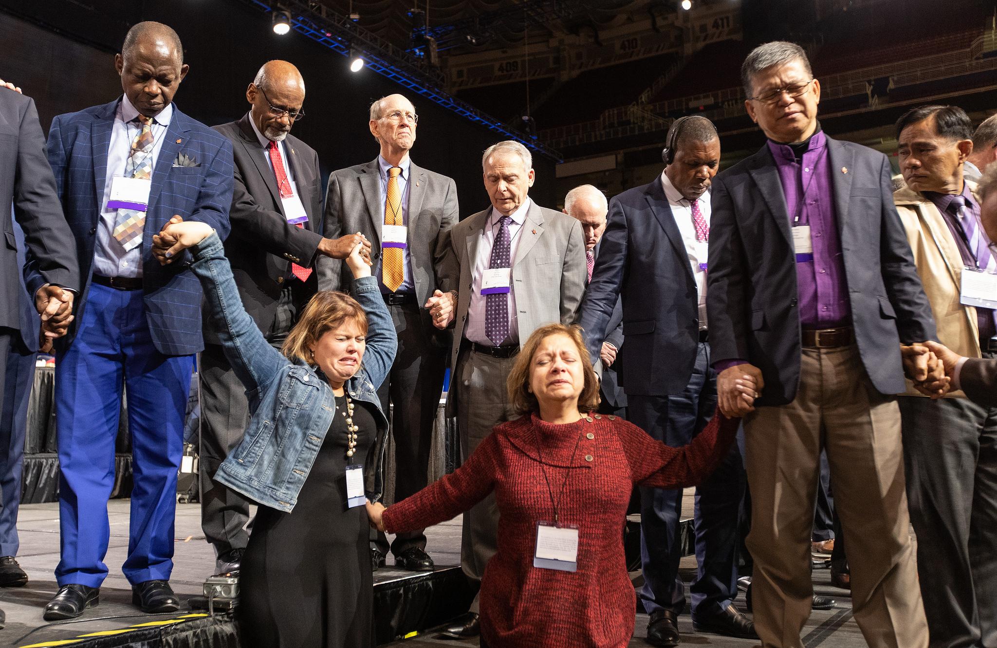 Os delegados da Flórida, Rachael Sumner (à esquerda) e a Revda. Jacqueline Leveron (frente à direita) da Conferência da Flórida, juntam-se em oração com bispos e outros delegados na frente do palco antes de uma votação chave sobre as políticas da igreja a. Foto de Mike DuBose, UMNS.