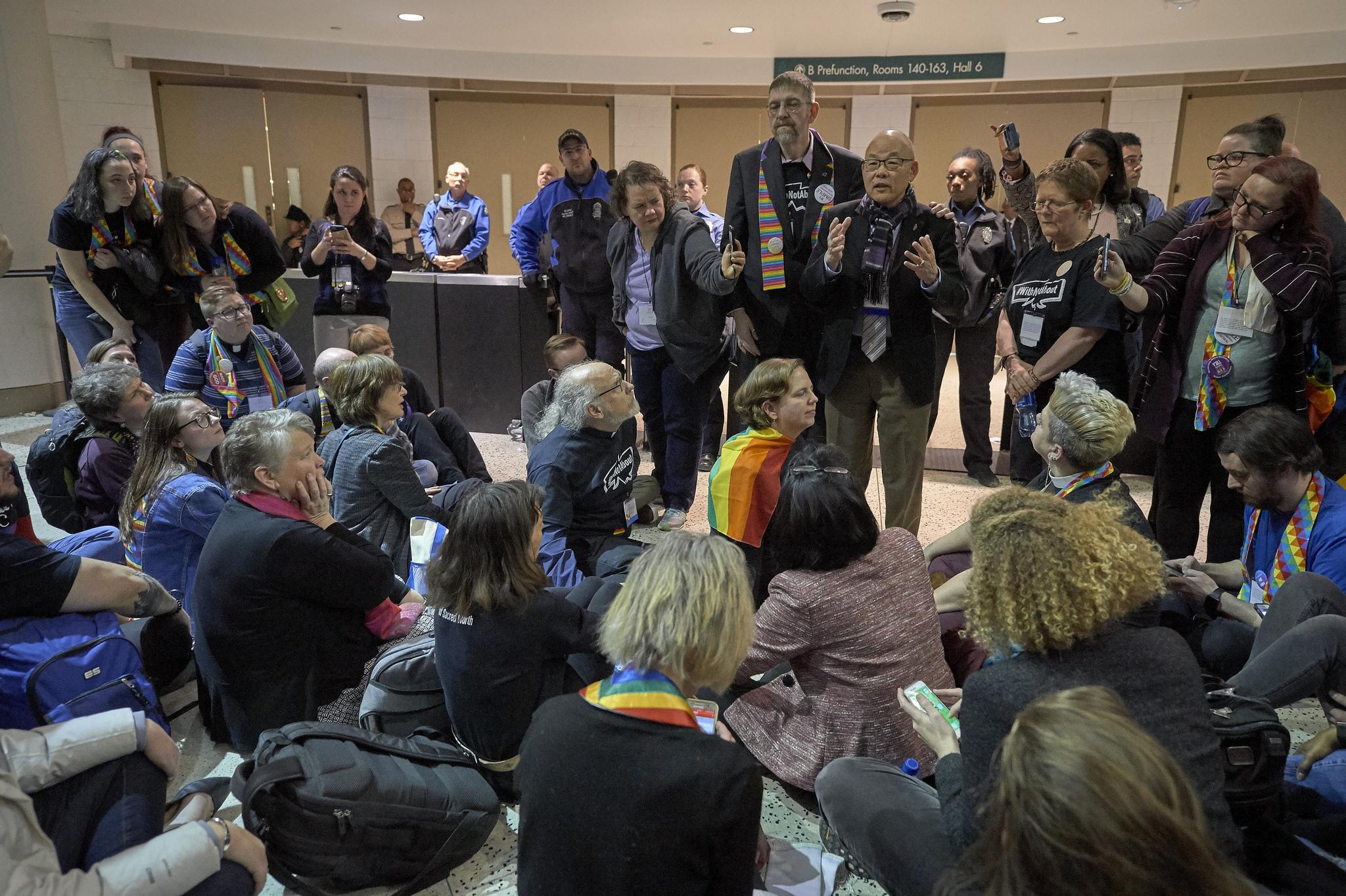 El obispo metodista unido Robert Hoshibata se reúne con manifestantes molestos por la aprobación del Plan Tradicional, que afirma las prohibiciones actuales de la iglesia de ordenar al clero LGBTQ y de oficiar o celebrar bodas entre personas del mismo sexo. La votación se realizó el último día de la Conferencia General de 2019, en San Luis. Foto por Paul Jeffrey, SMUN.