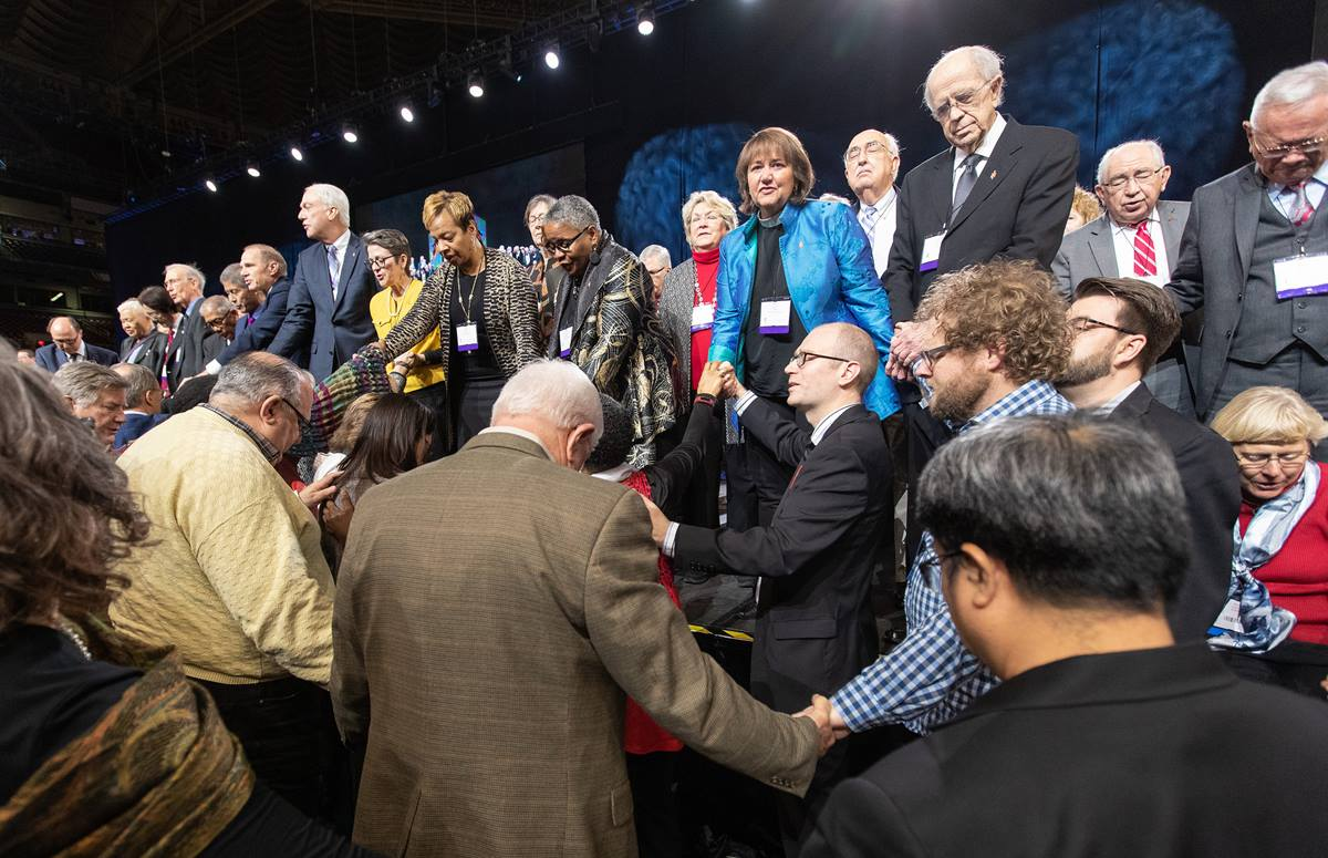 Delegates and bishops join in prayer at the front of the stage before a key vote on church policies about homosexuality during the 2019 United Methodist General Conference in St. Louis. Photo by Mike DuBose, UMNS.