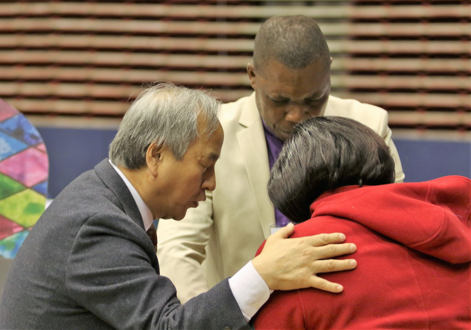 Bishop Hee-Soo Jung, left, prays with delegates during a Day of Prayer on the first day of General Conference 2019 in St. Louis. Photo by the Rev. Thomas Kim, UMNS.