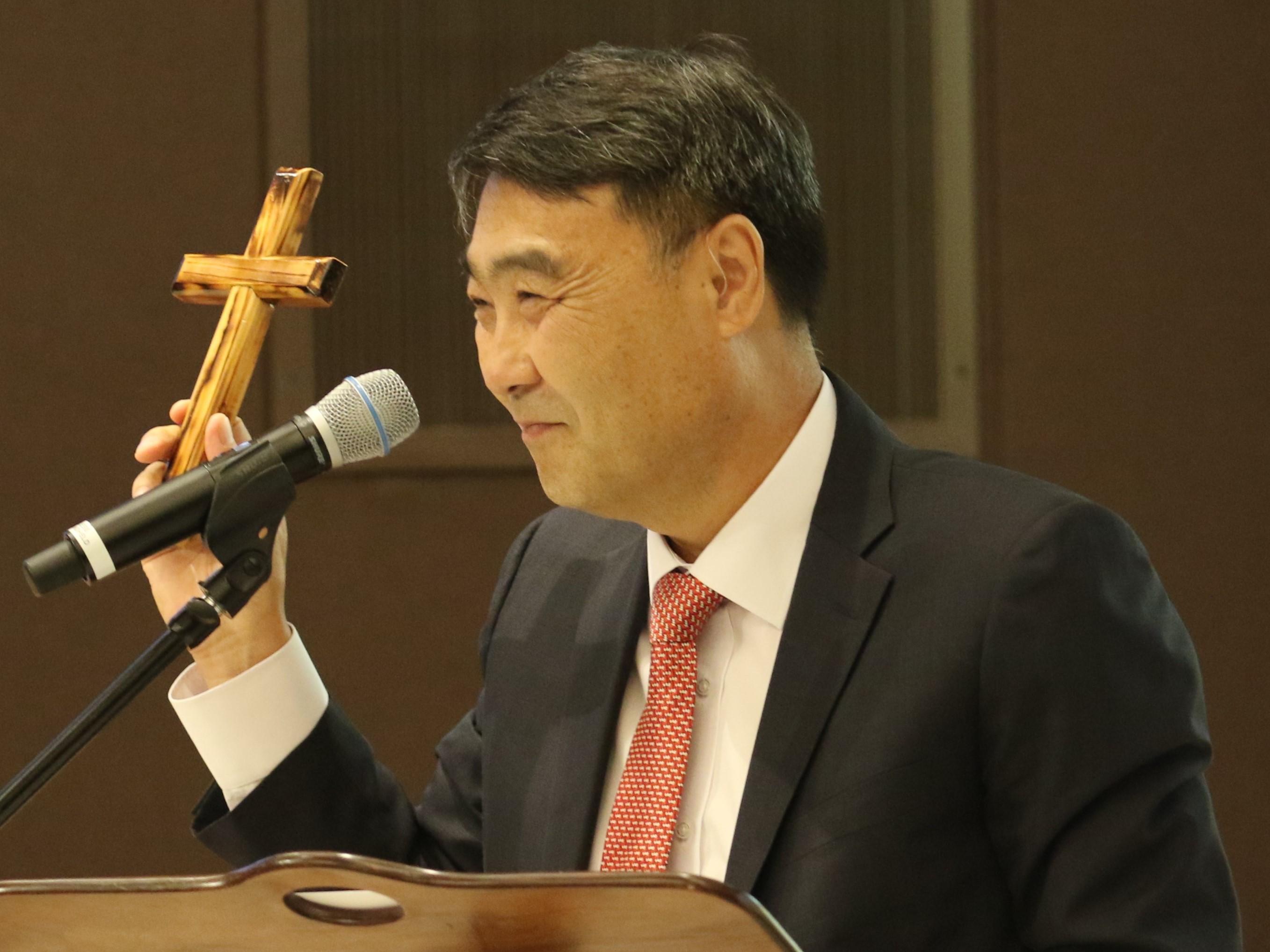 2018년 8월 와싱톤에서 열린 평화축제에서 김정호 목사가 설교 중에 북에서 만든 십자가를 들어 보이고 있다. 사진 김응선 목사, UMNS