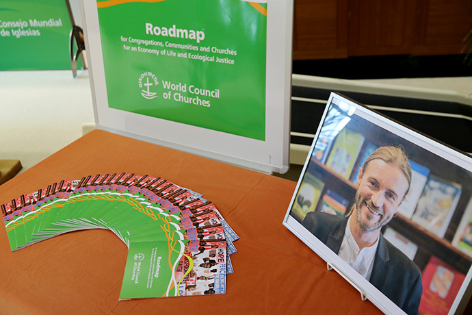 """A photo of the late Rev. Norman Tendis stands next to the environmental """"roadmap"""" he created for congregations on behalf of the World Council of Churches. Photo by Ivars Kupcis/WCC."""