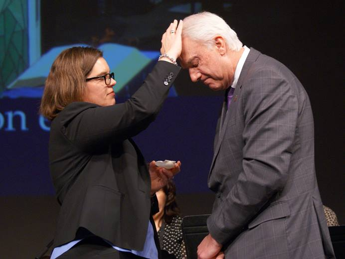 The Rev. Heather Sinclair anoints Bishop Thomas J. Bickerton at the beginning of a time of healing prayer and anointing at the close of a special session of the New York Annual Conference at Purchase College, State University of New York. Photo by Stephanie Parsons.
