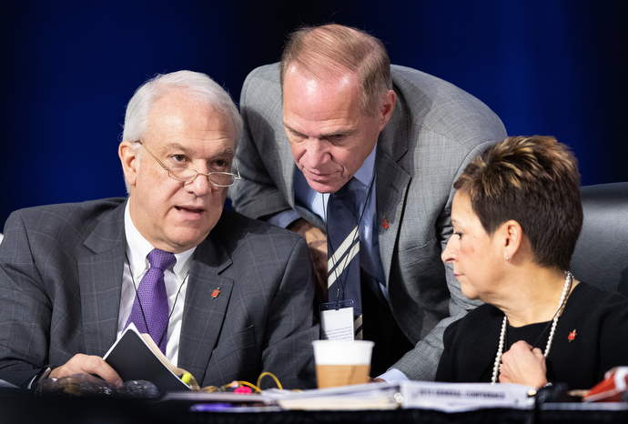 """Bishops confer during the 2019 United Methodist General Conference in St. Louis. From left are Bishops Thomas Bickerton, John Schol, and Cynthia Fierro Harvey. Bickerton, a member of the Commission of General Conference and a member of the task force that will be looking into potential voting irregularities, said integrity is his primary concern. """"It is disappointing to think there has been any kind of impropriety whatsoever."""" Photo by Mike DuBose, UMNS."""