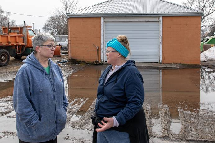 The Revs. Terra Amundson (left) and Catie Newman of the Iowa Conference discuss church response to flooding in the Missouri River basin in Hornick, Iowa. Amundson is superintendent of the Southwest District and Newman is disaster response coordinator for the conference. Photo by Arthur McClanahan, Iowa Conference.