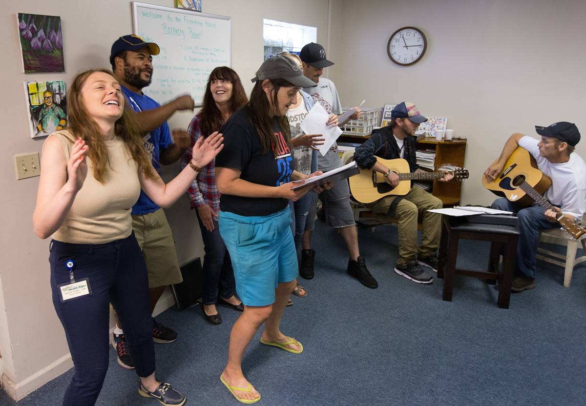 Program director Caitlin Sussman (left) joins in singing with the Voices of Hope choir at Friendship House, a mental health drop-in center in Morgantown, W.Va.