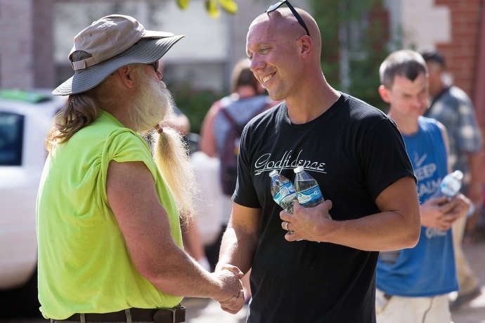 The Rev. Ross Thornton (right) visits with Ronald South while handing out water and praying with clients of the city mission in Huntington, W.Va. Thornton, a 2018 winner of a Denman Award for evangelism, runs a street ministry and pastors Fourth Avenue United Methodist Church in Huntington. Photo by Mike DuBose, UMNS.