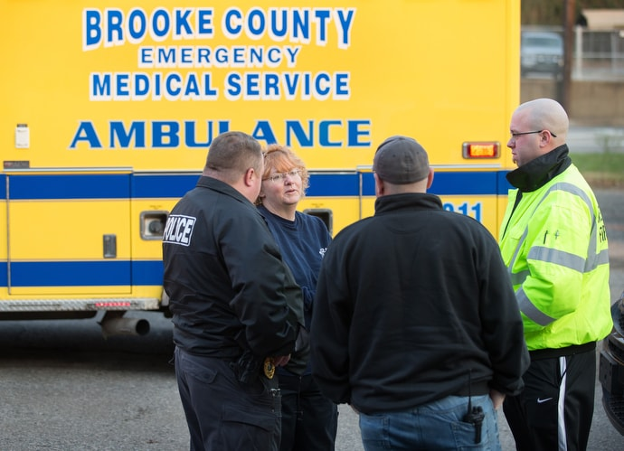 EMT Deb Dague (second from left) speaks with police and fire officials during a medical call in Wellsburg, W.Va. Photo by Mike DuBose, UMNS.