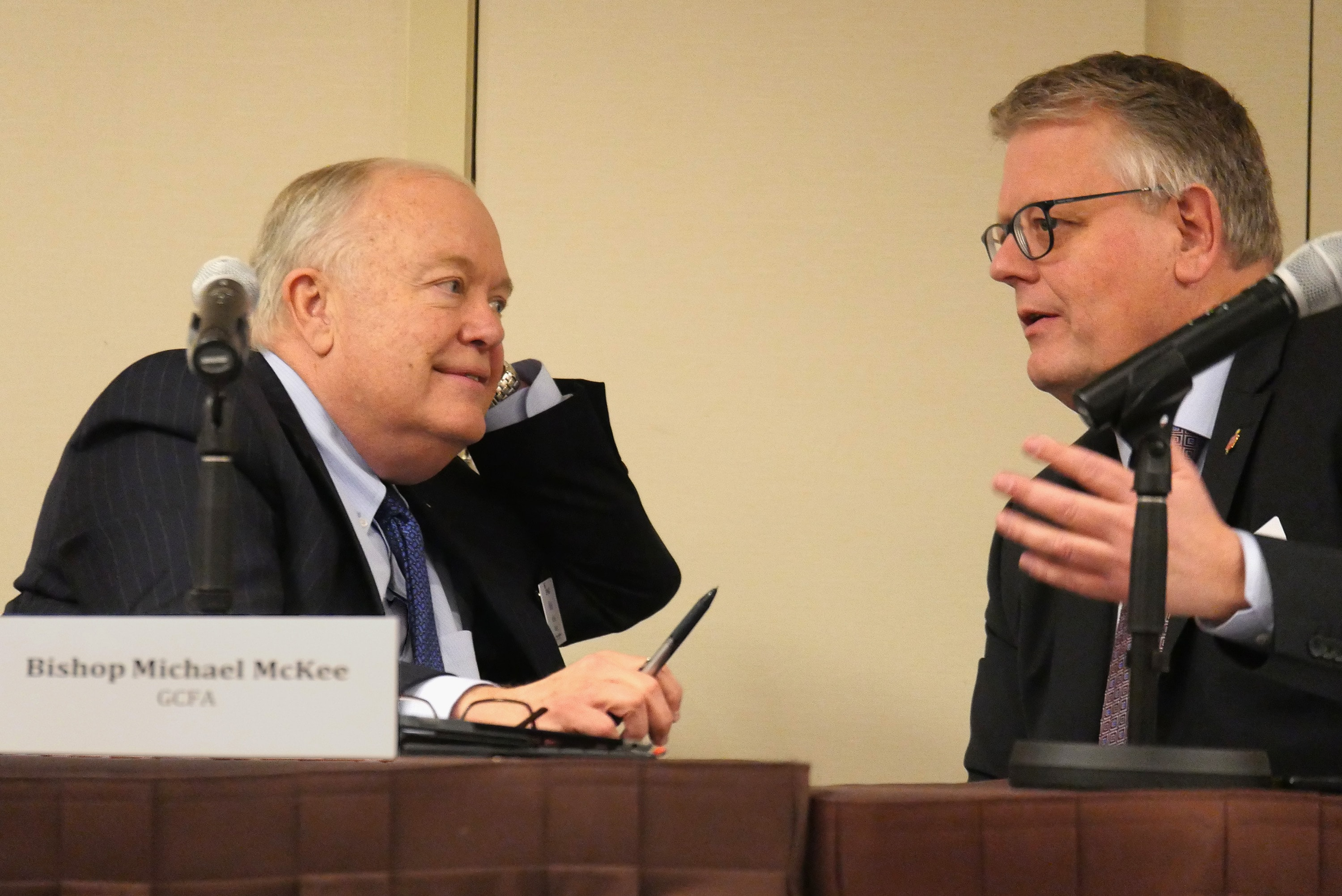 Bishops Mike McKee and Christian Alsted discuss the process for voting on budget proposals during a joint meeting of the General Council on Finance and Administration board and Connectional Table in Nashville, Tenn. McKee is president of the finance agency board and Alsted is chair of the Connectional Table. Photo by Heather Hahn, UMNS.