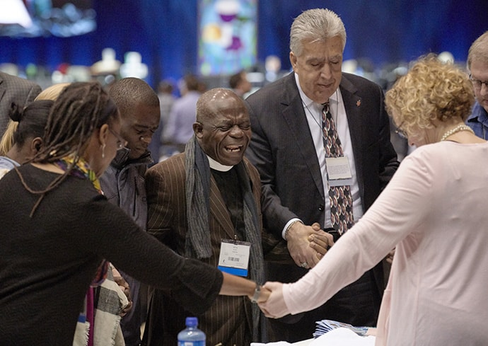 Delegates pray together during the Feb. 23, 2019, opening session of the Special Session of the General Conference of The United Methodist Church. In the center is the Rev. Jerry Kulah a supporter of the Traditional Plan from Liberia. Photo by Paul Jeffrey, UMNS.