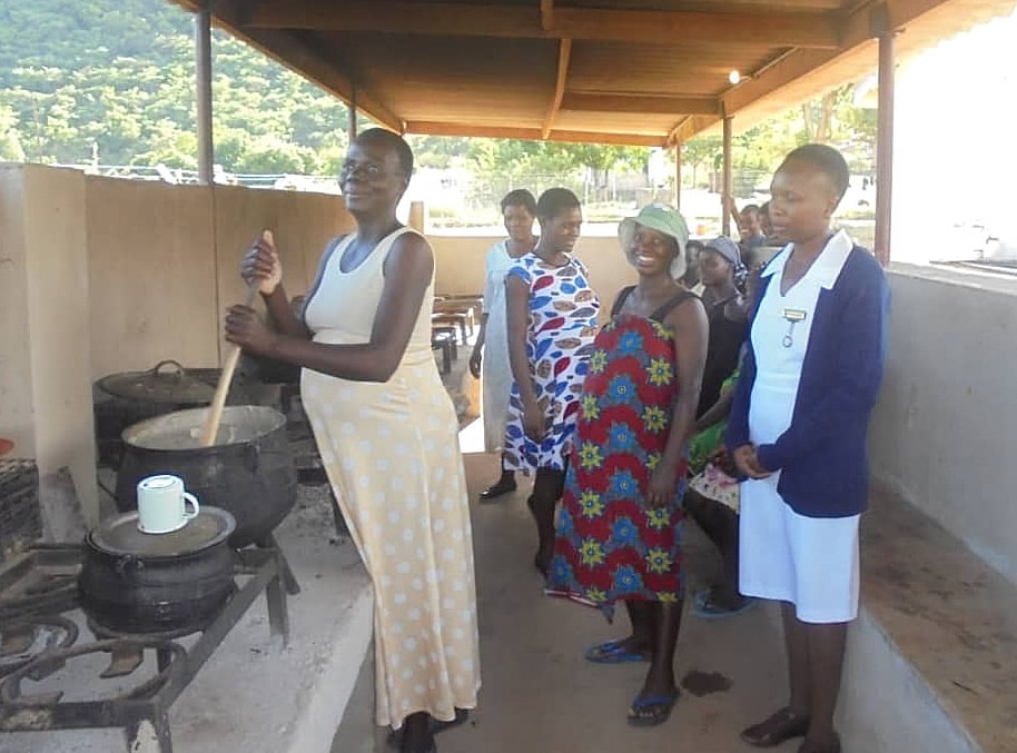 Mothers-to-be cook together in an open-air kitchen at the new mothers' shelter in Mutare, Zimbabwe. The shelter for high-risk mothers was completed with a grant from the United Methodist Board of Global Ministries. Photo by Kudzai Chingwe, UMNS.