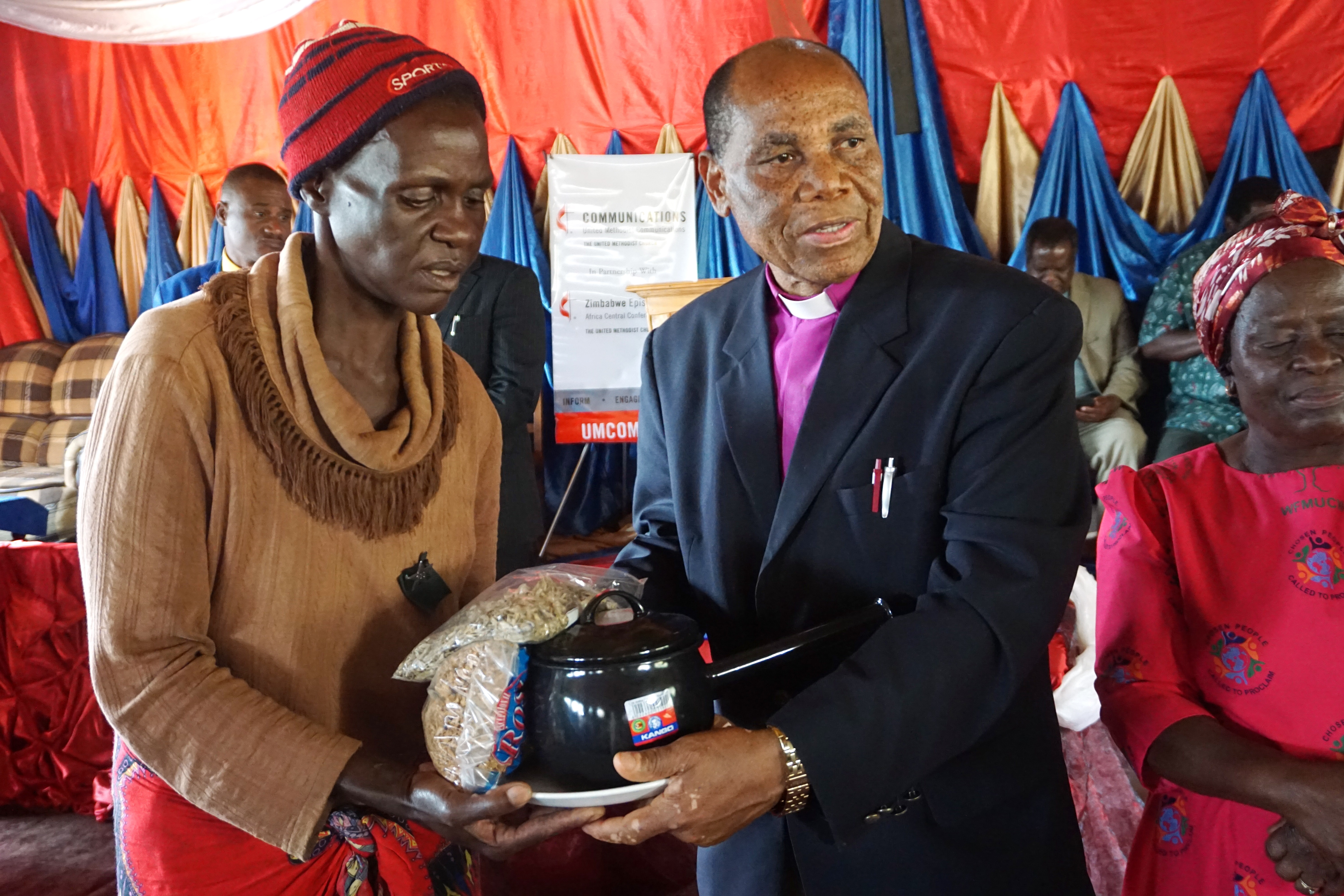Cyclone survivor Josephine Mutambambishi receives supplies from Bishop Eben K. Nhiwatiwa in Ngangu, Zimbabwe. The bishop and other church leaders visited the hard-hit area in the Chimanimani District in late April. Photo by Kudzai Chingwe, UMNS.