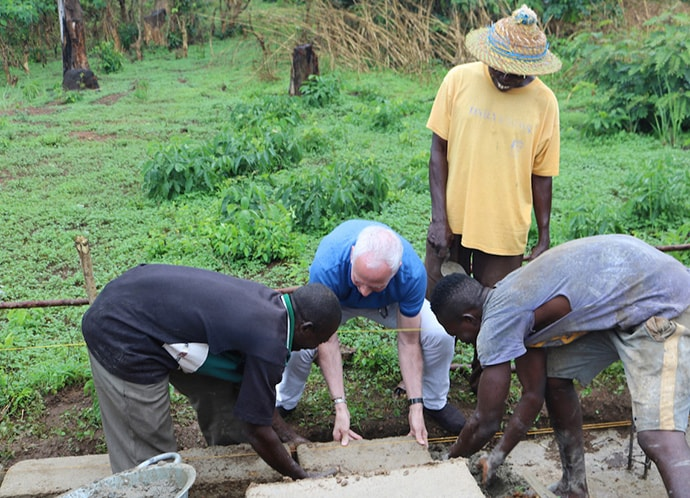 The Rev.  Gary Weaver, senior pastor of Camp Hill United Methodist Church in Camp Hill, Pennsylvania, helps to lay one of the first bricks for a new three-classroom building during a groundbreaking ceremony April 27 in Panguma, Sierra Leone. The new structure will help with overcrowding at the village's Lower Bambara Secondary School. Photo by Phileas Jusu, UMNS.