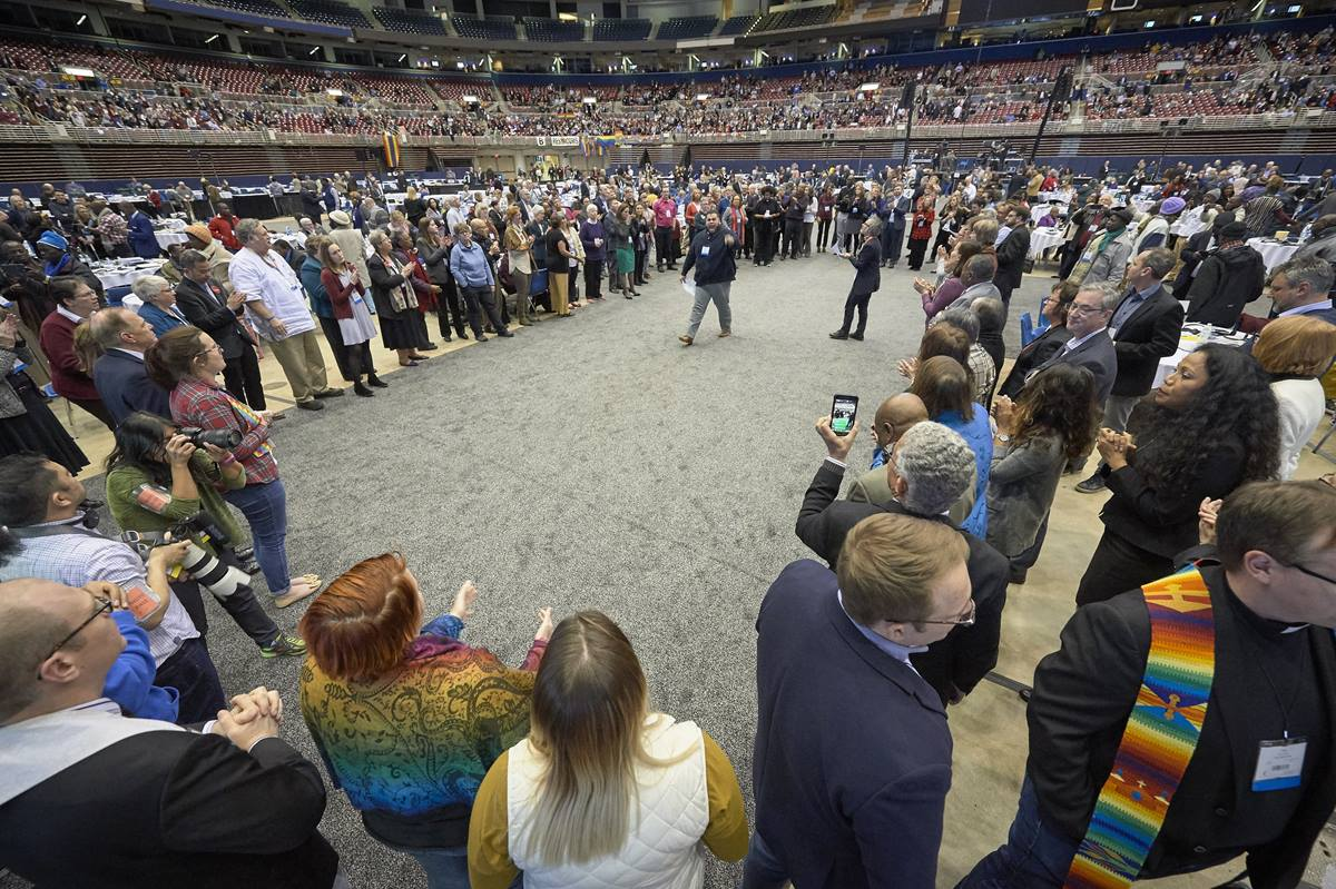 After a Feb. 26, 2019, vote to strengthen church policies about homosexuality, delegate Ian Urriola from New York speaks to other delegates who, in protest, formed a large circle in the center of the plenary floor. Photo by Paul Jeffrey, UMNS.