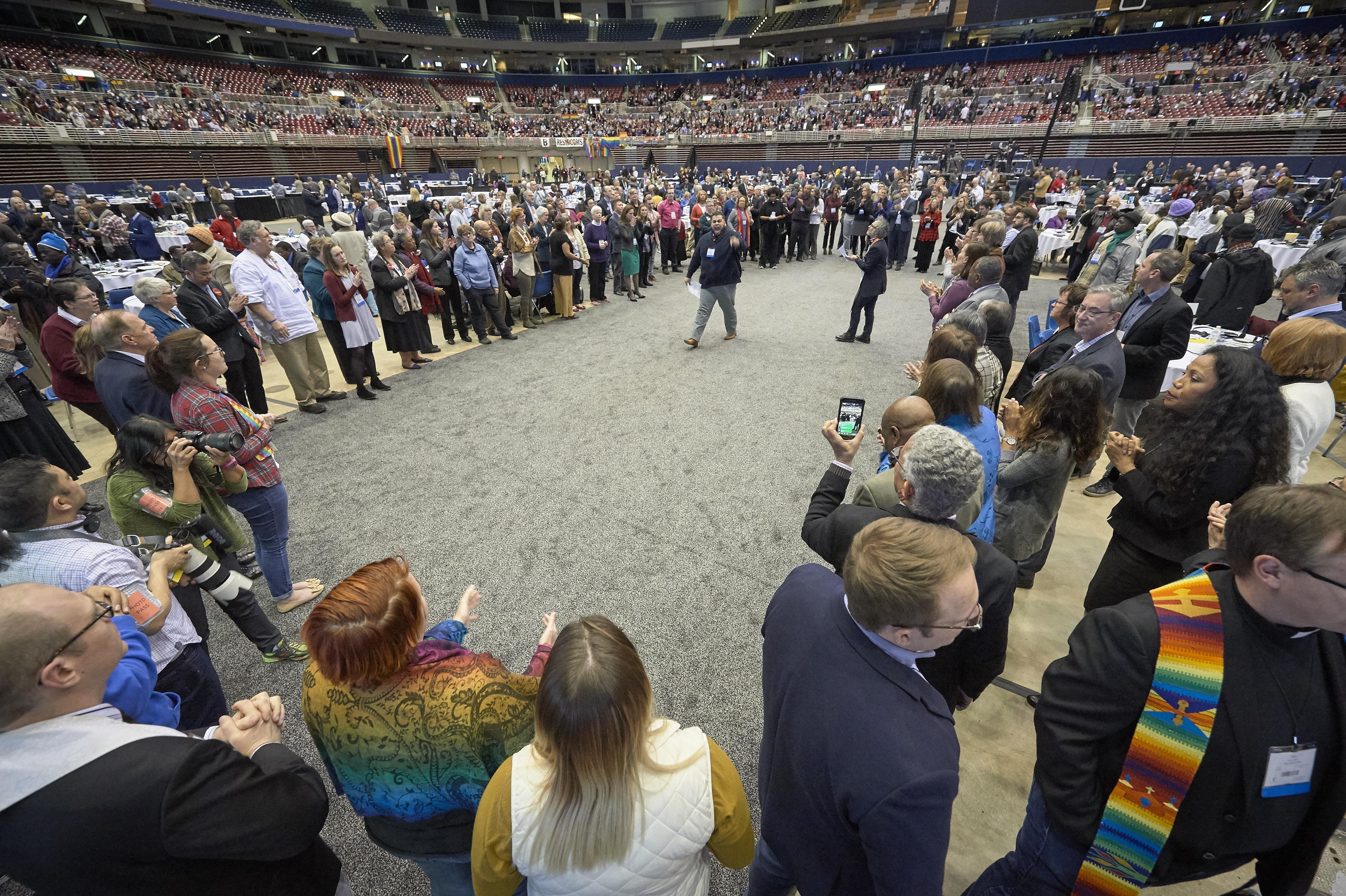 Depois da votação de 26 de fevereiro de 2019, que fortaleceu as políticas da igreja sobre a homossexualidade, o delegado Ian Urriola de Nova York fala com outros delegados que, em protesto, formaram um grande círculo no centro do plenário. Foto de Paul Jeffrey, Notícias MU.