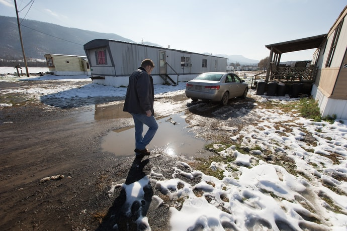 Wayne Worth makes his way through a trailer park in Fisher, W.Va., while going door to door with resource information for people struggling with addiction. The flyers include numbers for 844-HELP4WV, a statewide hotline for anyone needing addiction support.