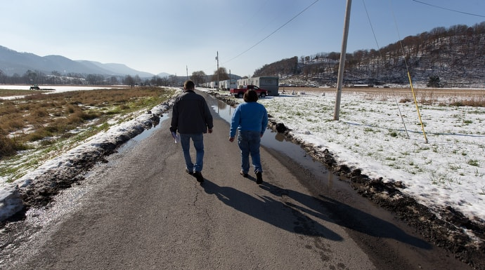 Wayne Worth (left) and the Rev. Cheryl George walk through a trailer park in Fisher, W.Va., while handing out resource information for those struggling with addiction.