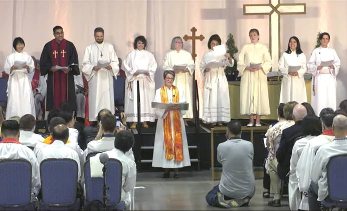 The ordination and commissioning service at the Northern Illinois Conference at the Renaissance Schaumburg Convention Center in Schaumburg, Ill., on Sunday, June 2, 2019. The conference ordained two deacons and seven elders, including an openly transgender deacon. Four were commissioned as provisional deacons, including two openly LGBTQ candidates. Two candidates were commissioned as provisional elders. Video image courtesy of Northern Illinois Conference livestream.