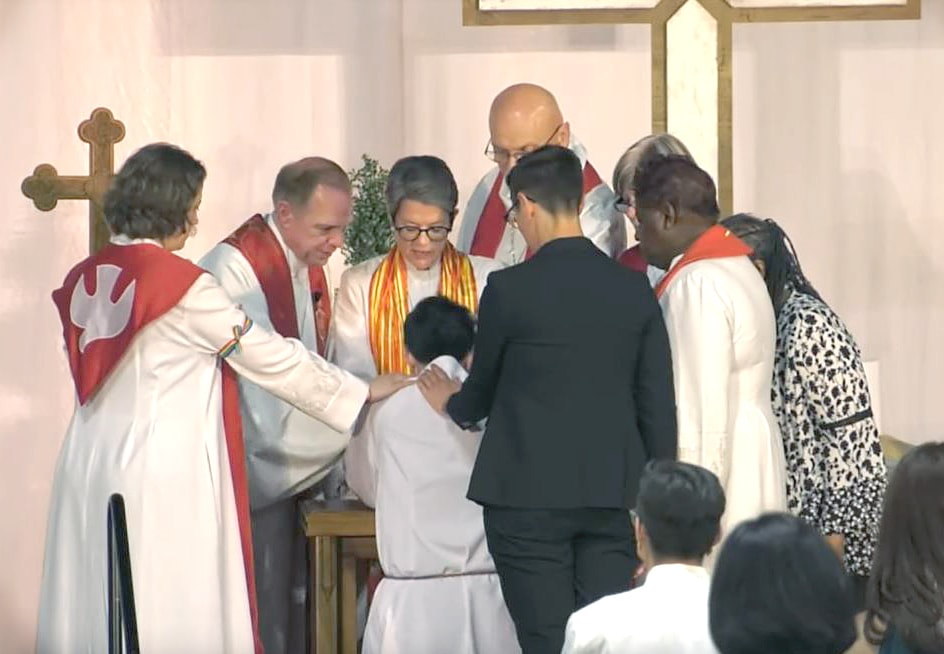 Northern Illinois Bishop Sally Dyck lays hands on the Rev. M Barclay, ordaining Barclay as a deacon in full connection. The cabinet and Barclay's partner and sponsor, the Rev. Anna Blaedel, also surround the new deacon to pray. Video image courtesy of Northern Illinois Conference livestream.