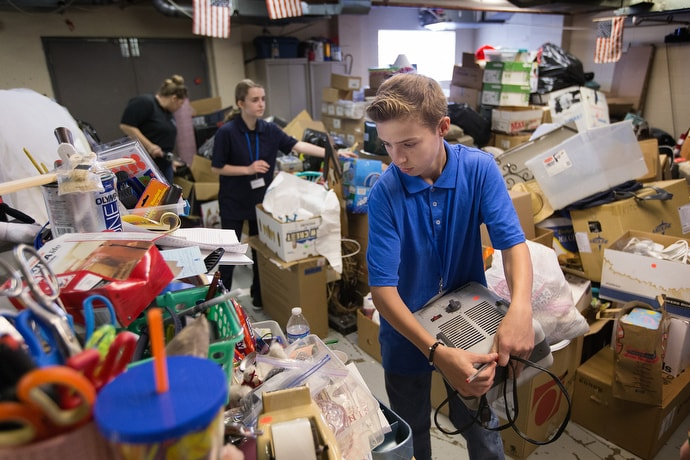 Skyler (front) helps sort donated household goods that will be sold in the thrift store at House of the Carpenter in Wheeling, W.Va. He was among a group of middle school students taking part in House of the Carpenter's Pre-Work Camp. Photo by Mike DuBose, UM News.