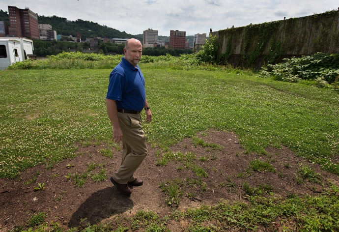 The Rev. Mike Linger describes plans to expand House of the Carpenter into a vacant lot next door to the present facility in Wheeling, W.Va. Photo by Mike DuBose, UM News.