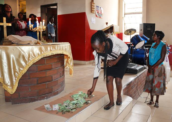 Rufaro Chisenga places her offering on the altar at St. Paul United Methodist Church in Harare, Zimbabwe. Despite the country's economic turmoil, pastors say members are continuing to give to the church. Photo by Priscilla Muzerengwa, UM News.