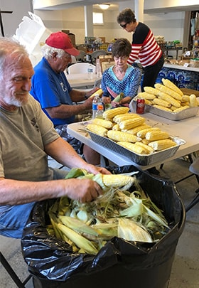 Volunteers shuck corn at Clarksville United Methodist Church, which has provided meals to those affected by flooding or working to fortify the town against an overflowing Mississippi River. From left are Bill Blakey, Bob Frank, Linda Frank and Jo Anne Smiley, Clarksville's mayor. Photo by Janie Busch.