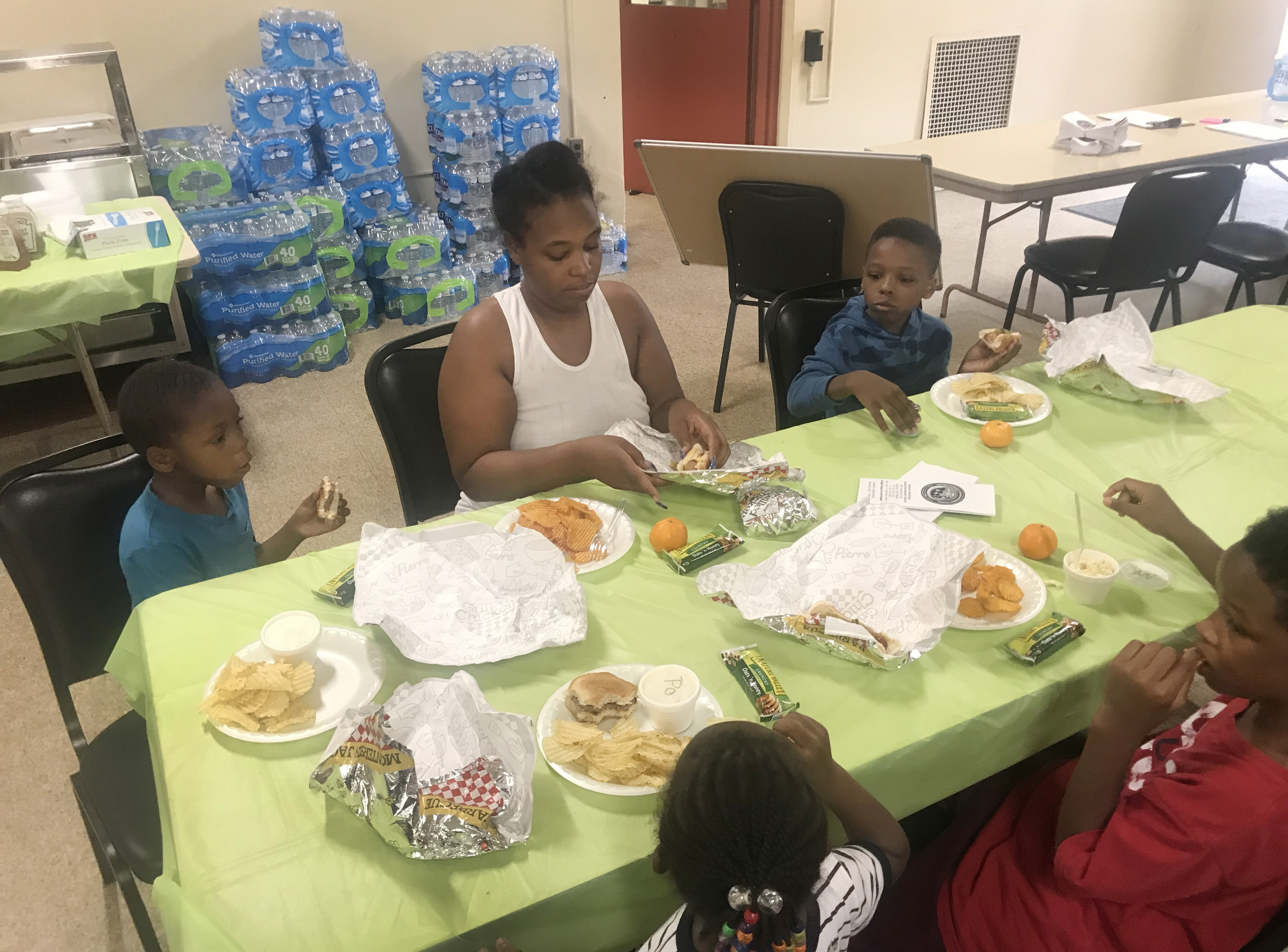 An unidentified woman eats with her children at McKinley United Methodist Church in Dayton, Ohio. The church offered shelter, hot food, free Wi-Fi, cases of water, electricity and clothes. Photo by the Rev. Peter Edward Matthews.