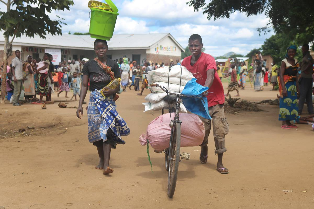 Shiku Kajalukapushes carries relief items received from the Malawi United Methodist Church on his bicycle. With him are his wife and baby. Photo by Francis Nkhoma, UM News.