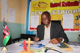 Felix Wandera handles paperwork at the United Methodist Church Savings and Credit Co-Operative Society in Nairobi, Kenya. Wandera is assistant president of the credit union, the first church-based financial institution in the East Africa Episcopal Area. Photo by Gad Maiga, UM News.