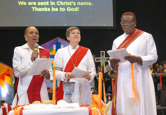 Newly ordained deacons lead the benediction at the end of the ordination service during the New York Annual Conference meeting at Hofstra University in Hempstead, N.Y. From left are the Revs. Arletha (Lisa) Miles Boyce, Lea A. Matthews and Janet L. Cox. Matthews says she sees her ministry as a helping hand to marginalized people in the world, including LGBTQ people like herself and her wife. Photo by Stephanie Parsons, NYAC.