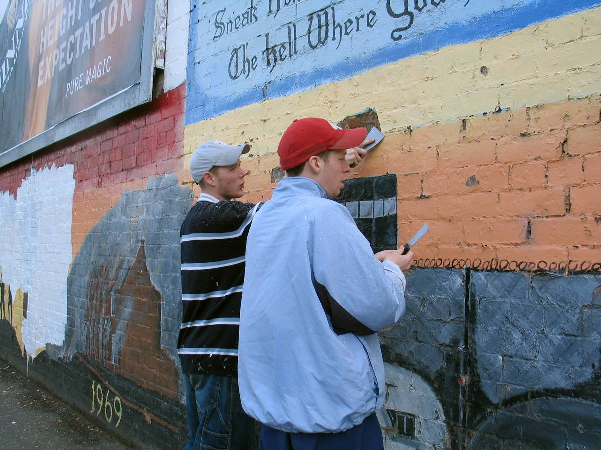 """Volunteers remove a traditional paramilitary mural from a wall in in Belfast, Northern Ireland, in 2003 to make way for a new mural that will honor both Catholic and Protestant heroes from the two World Wars. """"Brexit"""" — Britain's process of withdrawing from the 28-member European Union — is raising concerns about re-imposing hard borders on the island of Ireland. File photo by Kathleen LaCamera."""