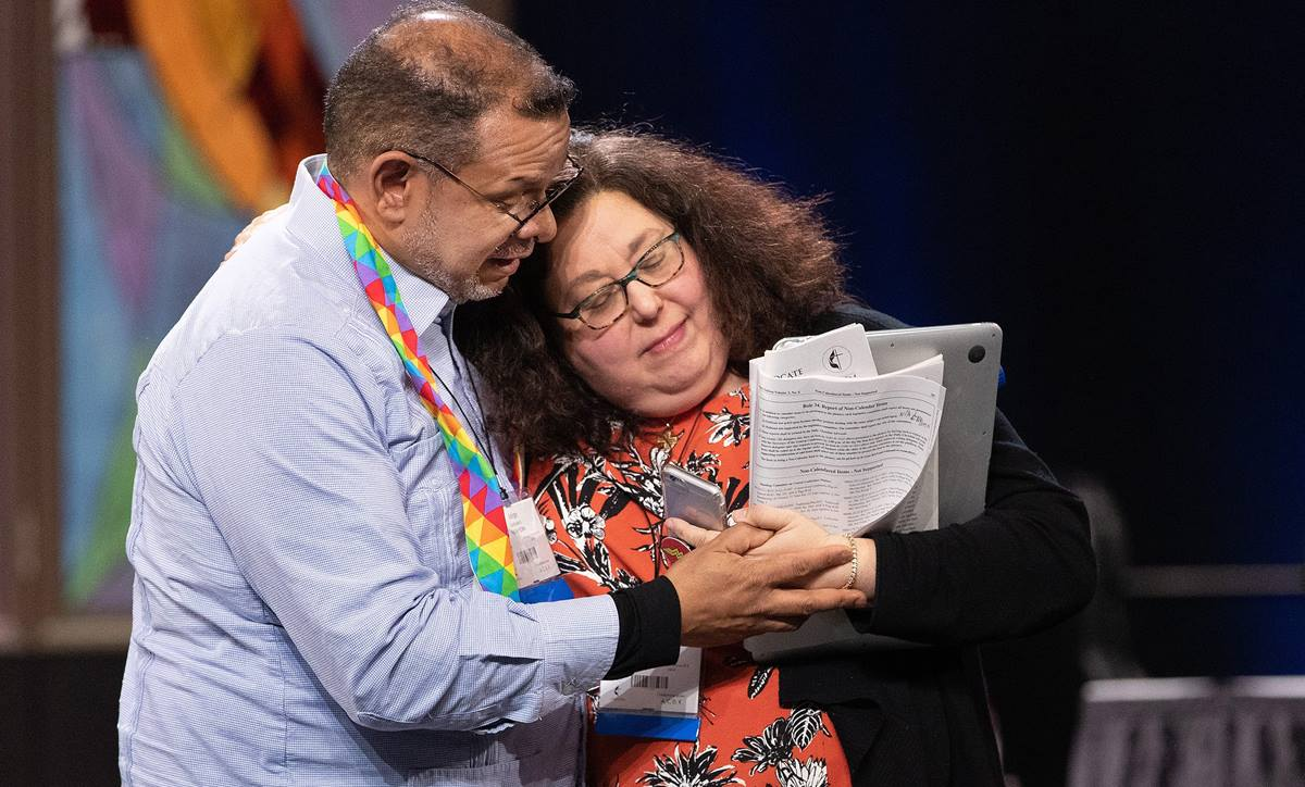 Delegates Jorge Lockward and the Rev. Beth Ann Cook embrace during the closing moments of the 2019 United Methodist General Conference in St. Louis. The two had previously spoken on opposite sides in a debate over possible church exit plans. U.S. conferences are calculating how much a church must pay if it leaves under legislation General Conference approved. File photo by Mike DuBose, UM News.