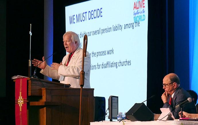 남조지아연회의 회계이자 은급 담당자인 데렉 맥알리어 목사는 조지아주 콜럼버스에서 열린 2019년 남조지아연회에서, 2019년 특별총회에서 통과된 탈퇴와 연금에 관한 내용을 시행하기 위한 연회 규정을 제안하며, 설명하고 있다. 그 옆에는 로슨 브라이언 감독이 앉아있다. 사진 제공 해더 한, UM News.