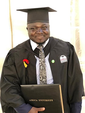 Vincent Yohanna proudly holds his diploma after graduating from Africa University. Photo courtesy of Africa University.