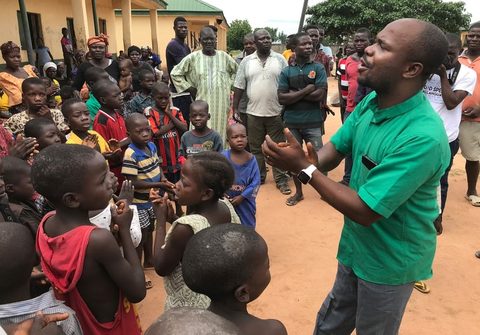 The Rev. Ande Emmanuel leads children in singing a church song at a camp for internally displaced persons in Jalingo, in northern Nigeria. The camp is one of 10 in Jalingo where The United Methodist Church provides ministerial support and supplies. Photo by Tim Tanton, UM News.