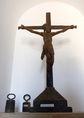 """A crucifix and weights that were attached to slaves' chains are on display at the Angola National Slavery Museum, near Luanda in 2006. The exhibit caption on the base of the crucifix reads """"Crucifix - religious instrument used by the missionaries, revealing their co-participation in the slave traffic."""" File photo by Mike DuBose, UM News."""