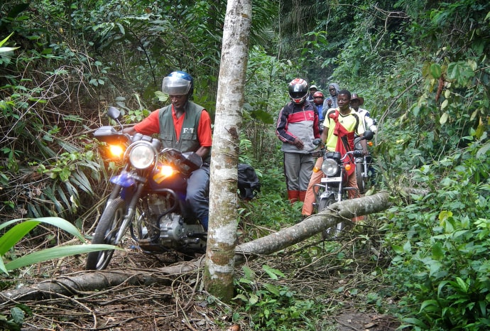 Motorcyclists carrying a United Methodist delegation make their way around a fallen tree near Tunda, Congo, in October 2015. Road conditions routinely make for difficult travel in Congo. File photo by Mike DuBose, UM News.