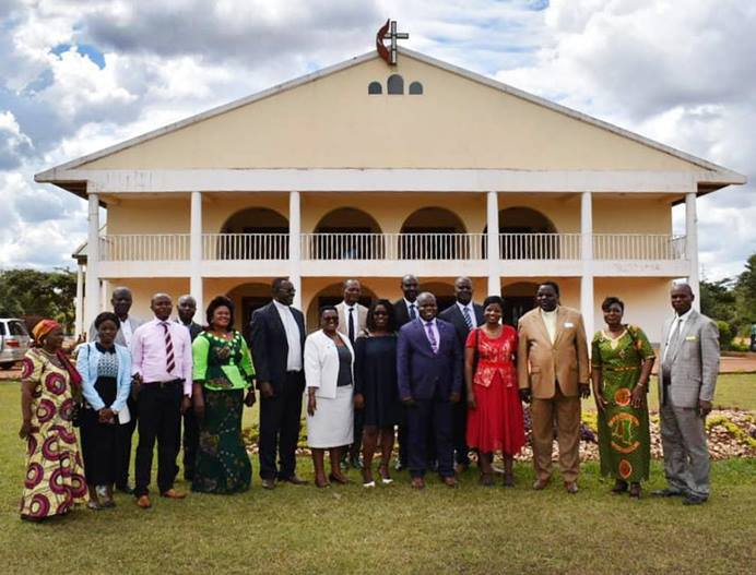 The Zimbabwe Episcopal delegation stand in front of Joli Site Church in Galilee during their visit in the South Congo Episcopal Area. Photo by Chenayi Kumuterera, UM News.
