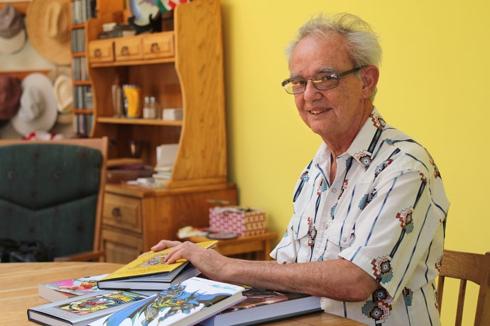 Mike Friedrich, shown at his home in Berkeley, Calif., shows off comic book stories he wrote as a young man. Today he is a United Methodist deacon in the Bay District of the California-Nevada Conference. Photo by Spud Hilton.