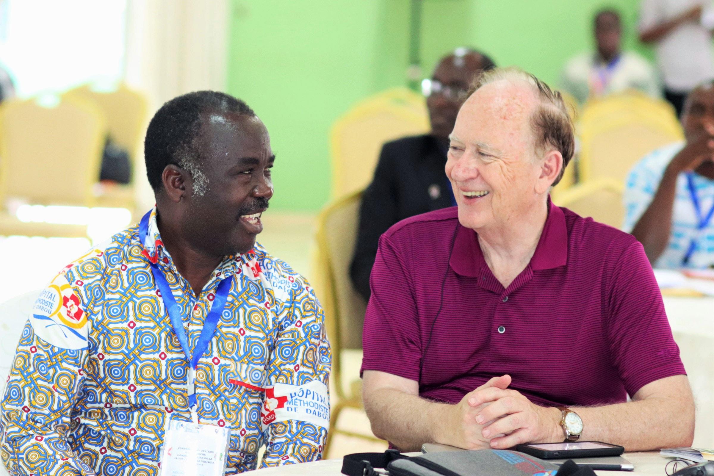 Le Dr Daniel Ahui (à gauche), directeur de l'Hôpital Méthodiste Uni de Dabou, et le Révérend Donald Messer, directeur exécutif de Center for Health and Hope, s'entretiennent pendant le sommet. L'hôpital de Dabou fournit des soins à 1 362 patients atteints du VIH. Photo de Isaac Broune, UMNS.