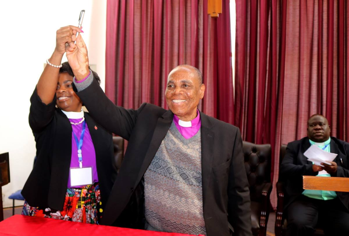 Bishops Cynthia Moore-Koikoi (left) of the Western Pennsylvania Conference and Eben K. Nhiwatiwa of the Zimbabwe Area celebrate the signing of a continuing partnership covenant between the two areas during the 2019 Laity Academy at Africa University in Mutare, Zimbabwe. Photo by Eveline Chikwanah, UM News.