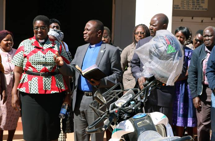 The Rev. Alan Masimba Gurupira (center), officiates a ceremony to present motorbikes to five pastors of the Mutasa Nyanga District of Zimbabwe on July 20. Listening are the Rev. Tafadzwa Musona (left, in red), district superintendent; and the Rev. Duncan Charwadza (right, behind bike), Connectional Ministries director and Deputy Administrative Assistant to the Bishop. The motorbikes were a gift from Mutasa Nyanga Homelink, a group of church members originally from the district, who pool their resources to support the pastors. Photo by  Eveline Chikwanah, UM News.