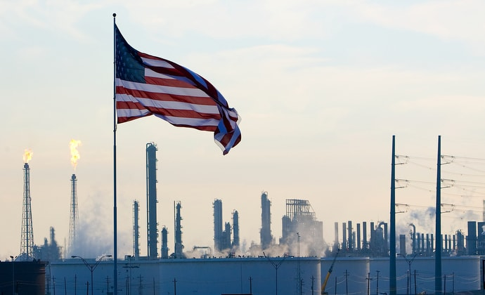 A U.S. flag flies above an oil refinery near Houston, Texas, in 2008. Wespath, the United Methodist pensions and benefits agency, is under pressure from environmental advocacy groups to divest from fossil fuel companies in response to concerns over climate change. File photo by Mike DuBose, UM News.