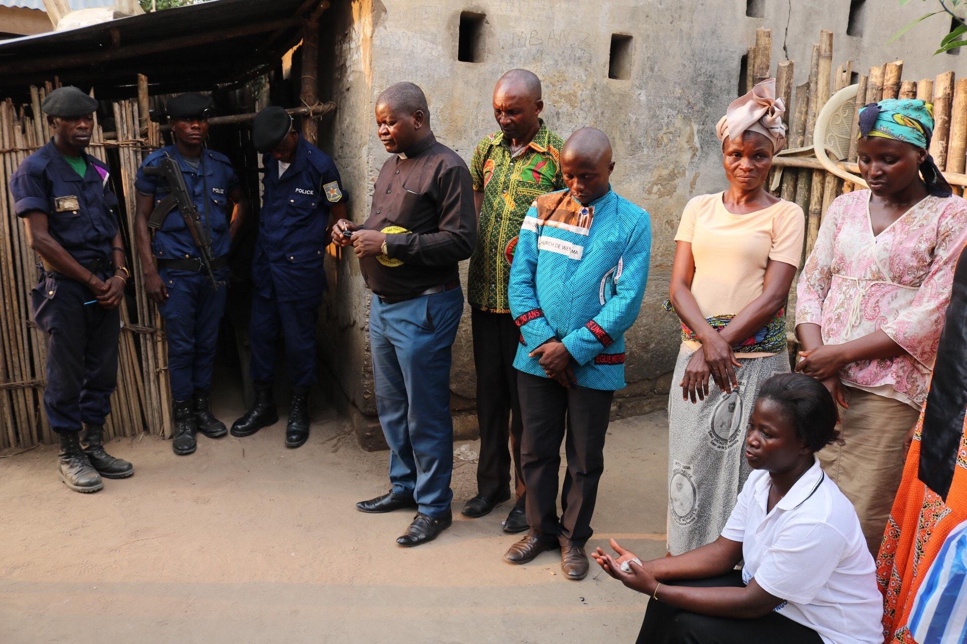 Le Rév. Robert Shuyaka Onakoy, chef de la délégation, dirige la prière dans la cour de la Prison Centrale de Lodja. Les membres de l'Église Méthodiste Unie de Lodja ont apporté de la nourriture à plus de 130 prisonniers. Photo de François Omanyondo, UM News.