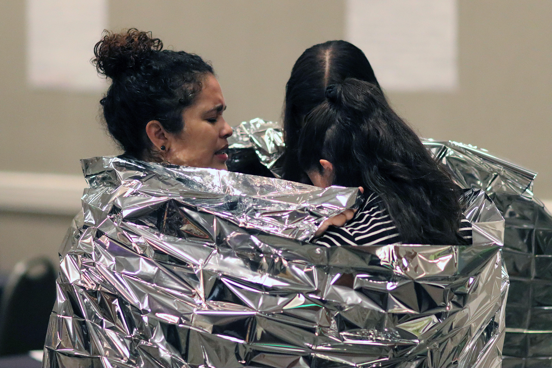 La Pastora Dorlimar Lebrón orando con dos jóvenes, envueltas en lel mismo tipo de mantas que cobijan a los/as niños/as y adultos/as inmigrantes que se mantienen detenidos, y algunos de ellos hacinados, en los centro de detención que ICE mantiene en la frontera. Foto por Michelle Maldonado, UMCOM.