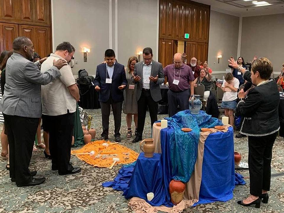 Liderados/as por la Obispa Cynthia Fierro-Harvey, los/as participantes en la plenaria elevan una oración y sus bendiciones  a un grupo de líderes que pudieran ser potenciales candidatos hispano-latinos al episcopado.  Foto: Michelle Maldonado, UMCOM.
