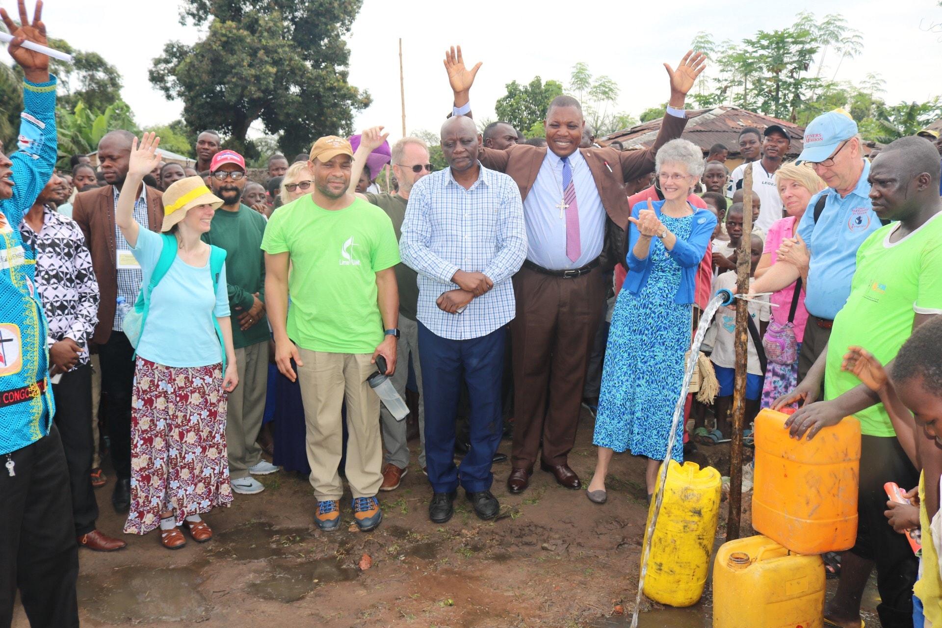 L'Evêque Daniel Lunge du Congo Central (en costume) et l'Evêque Peggy Johnson du Delaware (à sa gauche) se joignent à la population de Wembo-Nyama et du Delaware pour exprimer leur joie d'avoir de l'eau potable. La population de Wembo-Nyama a longtemps souffert des maladies dues à la mauvaise qualité de l'eau qu'elle consommait. Photo de François Omanyondo, UM News.