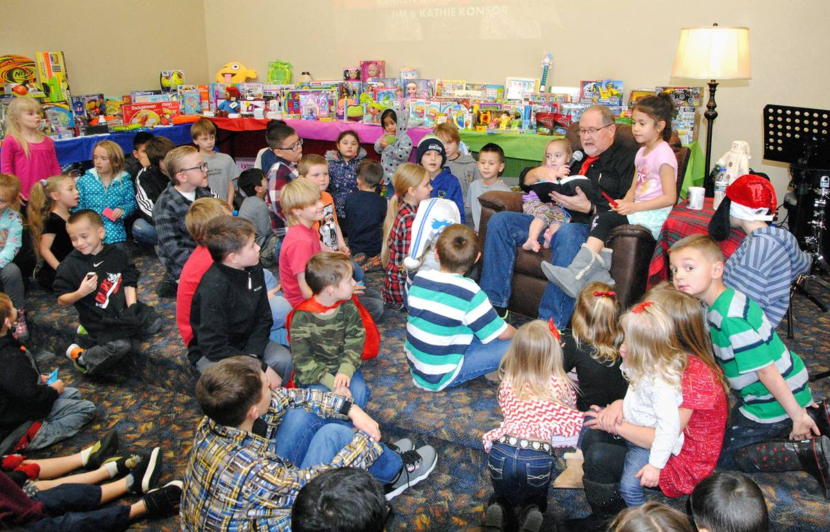 The Rev. James Konsor reads to children during a Christmas season event at the Bakken Oil Rush Ministry in Watford City, N.D. The ministry provides clothing, household items, furniture and more to needy families at a nominal price. Photo courtesy the Bakken Oil Rush Ministry.